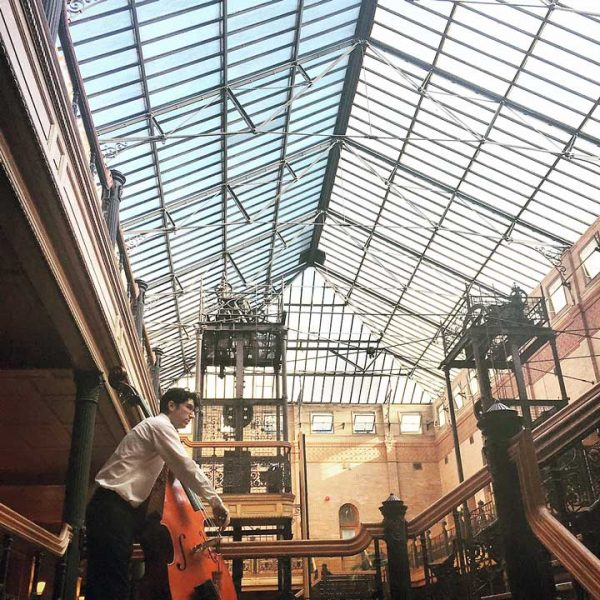 "Patrick plays upright bass in a mobile Opera ""Hopscotch"" in the legendary Bradbury Building, Los Angeles."